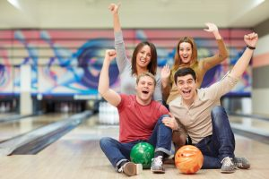 Emotional young people in bowling